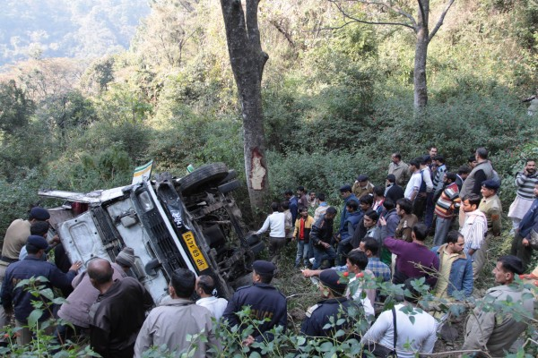 Police and locals try to rescue passengers from a bus which fell into gorge near Dharamsala on Dec.15, 2013. Two passengers were killed and 25 injured in the accident. (Photo: IANS)