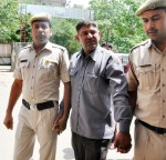 Gurgaon: Police take away Vinod, an Uber cab driver who was arrested for allegedly molesting a 21-year-old student before press in Gurgaon, on June 2, 2015. (Photo: IANS)